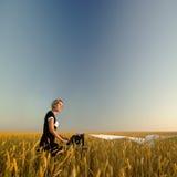 Jeune femme avec la machine à écrire dans le domaine du blé Image stock