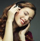 Jeune femme avec la musique de écoute d'écouteurs Photo stock