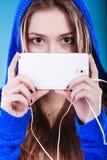 Jeune femme avec la musique de écoute de téléphone intelligent Image libre de droits