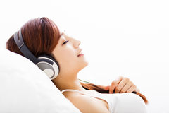 Jeune femme avec la musique de écoute d'écouteurs Photos stock