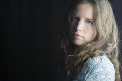 Jeune femme avec la peau juste, les yeux bleus et les cheveux bouclés brun clair dans l'éclairage dramatique Photographie stock libre de droits