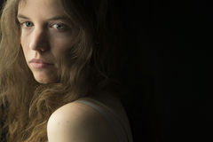 Jeune femme avec la peau juste, les yeux bleus et les cheveux bouclés brun clair dans l'éclairage dramatique Photographie stock