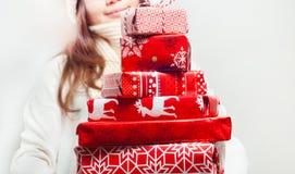 Jeune femme avec la pile des cadeaux bien emballés de Noël Photos stock