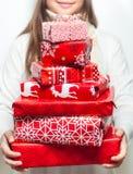 Jeune femme avec la pile des cadeaux bien emballés de Noël Photographie stock