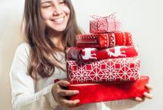 Jeune femme avec la pile des cadeaux bien emballés de Noël Images libres de droits