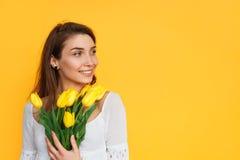 Jeune femme avec la pose jaune de tulipes Images libres de droits