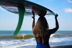 Jeune femme avec la promenade de planche de surf sur la plage noire de sable photographie stock libre de droits