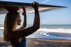 Jeune femme avec la promenade de planche de surf sur la plage noire de sable photos stock