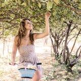Jeune femme avec la rétro bicyclette en parc Photo stock
