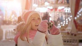 Jeune femme avec la rétro caméra au marché de Noël de la soirée d'hiver de neige banque de vidéos