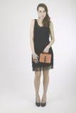 Jeune femme avec la robe noire semblant timide sur l'appareil-photo photographie stock
