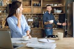 Jeune femme avec la tasse de smartphone et de café regardant l'homme avec la cuvette Photographie stock