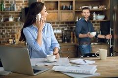 Jeune femme avec la tasse de smartphone et de café regardant l'homme avec la cuvette Images stock
