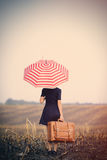Jeune femme avec la valise et le parapluie Photos stock