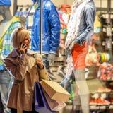 Jeune femme avec la ville de nuit de sacs à provisions photographie stock