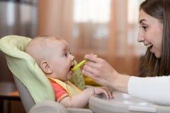 Jeune femme avec le bébé à la cuisine Le bébé s'assied sur la chaise du ` s de bébé La mère alimente l'enfant Photos stock