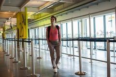 Jeune femme avec le bagage attendant dans le hall d'aéroport son avion Photos stock