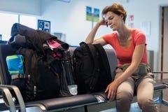 Jeune femme avec le bagage attendant dans le hall d'aéroport son avion Photo libre de droits