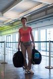 Jeune femme avec le bagage attendant dans le hall d'aéroport son avion Image libre de droits