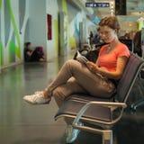 Jeune femme avec le bagage attendant dans le hall d'aéroport son avion Photographie stock