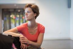Jeune femme avec le bagage attendant dans le hall d'aéroport son avion Photo stock