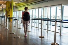 Jeune femme avec le bagage attendant dans le hall d'aéroport son avion Photos libres de droits
