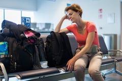Jeune femme avec le bagage attendant dans le hall d'aéroport son avion Photographie stock libre de droits