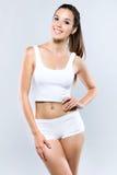 Jeune femme avec le beau corps posant sur le fond blanc Photographie stock