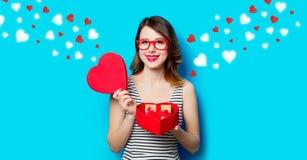 Jeune femme avec le cadeau à la boîte et aux coeurs abstraits Photo libre de droits