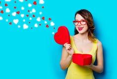 Jeune femme avec le cadeau et les coeurs abstraits Image stock