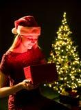 Jeune femme avec le cadeau, l'arbre de Noël et le fond décoratif de bokeh d'éclairage Elf et sapin avec des décorations image libre de droits