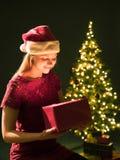 Jeune femme avec le cadeau, l'arbre de Noël et le fond décoratif de bokeh d'éclairage Elf et sapin avec des décorations photo stock