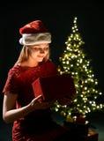Jeune femme avec le cadeau, l'arbre de Noël et le fond décoratif de bokeh d'éclairage Elf et sapin avec des décorations photo libre de droits