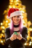 Jeune femme avec le cadeau, l'arbre de Noël et le fond décoratif de bokeh d'éclairage Elf et sapin avec des décorations photos libres de droits