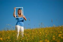 Jeune femme avec le cadre de tableau dans la campagne au printemps Photos libres de droits