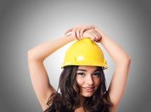 Jeune femme avec le casque antichoc de hellow contre le gradient Photographie stock libre de droits