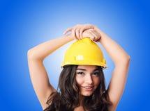 Jeune femme avec le casque antichoc de hellow contre le gradient Image libre de droits