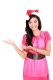 Jeune femme avec le chapeau de Santa montrant l'espace vide Photos stock