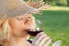 Jeune femme avec le chapeau du soleil buvant du vin rouge Image libre de droits