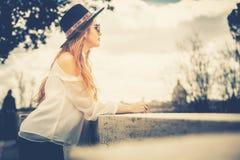 Jeune femme avec le chapeau et les lunettes de soleil se reposant dans la ville Image libre de droits