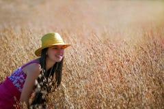 Jeune femme avec le chapeau se tenant sur le champ d'avoine Images stock