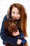 Jeune femme avec le chien de Labrador dans la forêt d'hiver Photographie stock
