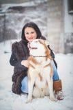 Jeune femme avec le chien de loup dans le chien de traîneau de neige Photos stock