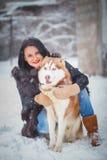 Jeune femme avec le chien de loup dans le chien de traîneau de neige Photo libre de droits