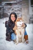 Jeune femme avec le chien de loup dans le chien de traîneau de neige Photographie stock