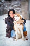 Jeune femme avec le chien de loup dans le chien de traîneau de neige Photo stock