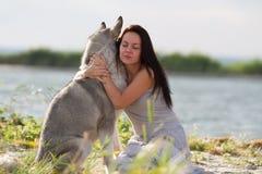 Jeune femme avec le chien de malamute d'Alaska Image stock