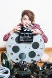 Jeune femme avec le clapet de film derrière la grande bobine de cinéma Image stock
