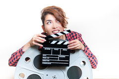 Jeune femme avec le clapet de film derrière la grande bobine de cinéma Photographie stock