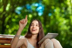 Jeune femme avec le comprimé numérique en parc Photo stock